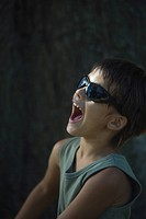 Little boy in sunglasses shouting, side view