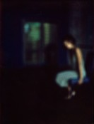 Woman sitting in dark room, defocused