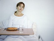 Woman sitting up in hospital bed, looking away from meal tray
