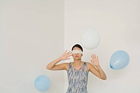 Woman blindfolded, hands raised, balloons floating around her