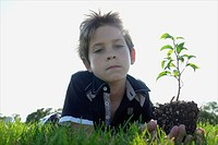 Low angle 8 year old boy lying on grass holding small tree, Winnipeg, Canada