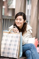 Young woman sitting on the outdoor chair holding her shopping bags