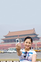 Young woman taking photograph in front of Tiananmen Square