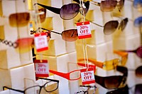 Discount signs hanging from sunglasses in a store