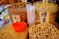 A variety of nuts, including peanuts, walnuts, and cashew nuts, on display in large plastic bags