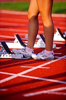 Female athlete standing beside the track starting block