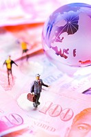Little toy figurines standing on the paper money around a globe