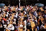 Menschen hist., Gesellschaft, Blick von oben auf Biergarten, Menschen an Holztischen sitzend und Bier trinkend, 80er Jahre, im freien sitzend