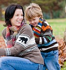 Young boy and mother playing together outdoors in autumn, Vancouver, British Columbia