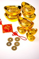 Close_up of gold ingots, tassel and Chinese coins