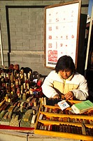 Chinese woman working on a stamp stone at a stamp stall in Panjiayuan Antique Market, Beijing, China