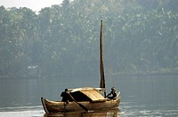 ASHTAMUDI LAKE IN MORNING LIGHT WITH LONE COUNTRY BOAT KOLLAM KERALA