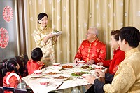 Family members in traditional clothes having dinner together and looking at young woman