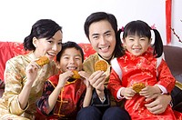 Young family with two children in traditional clothes holding the moon cakes and smiling at the camera