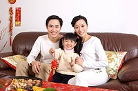 Young couple with one child holding a tassel, sitting on the sofa and smiling at the camera