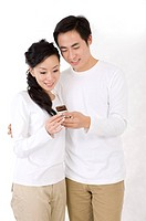 Young couple standing together and looking at the mobile phone, smiling