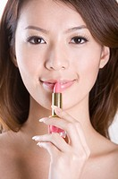 Young woman applying lipstick on the lip, portrait
