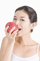 Young woman eating a red apple, portrait