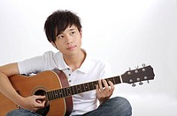 Young man playing guitar and looking away, portrait
