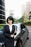 Businesswoman holding document folder and standing with vehicle
