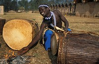 Drummer heating the drums before playing, Intore dance group at the National museum of Rwanda, Butare, Rwanda