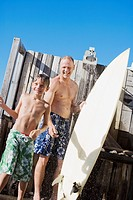 Father and son with surfboard rinsing off outdoors