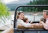Family sitting in jeep near lake