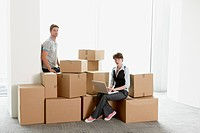 Business people sitting on boxes in empty office