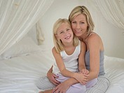 Mother and daughter hugging on bed