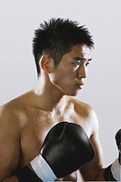 Japanese boxer wearing gloves and sweating