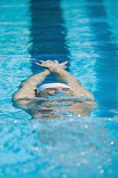 Young swimmer doing backstroke underwater