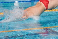 Australian swimmer diving for breaststroke competition swimming pool
