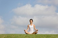 Young Woman sitting on grass in sukhasana position