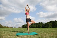 Young Woman doing the tree pose on mat