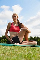 Young Woman doing yoga and stretching on mat