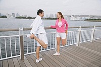 Young couple smiling and stretching legs on Bridge