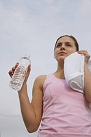 Young Woman holding water bottle and wiping face with towel