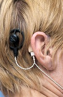Cochlear implant. Close_up of a cochlear implant being worn by a woman. The sound processor beige sits just behind the ear and the transmitter round, ...