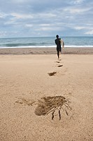 Man running on sand towards sea with leaving his footprints on beach