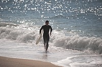 Young man running along shoreline with his surfboard