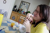 Teenage girl trying to open jamjar