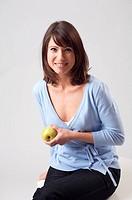 Junge Frau haelt einen Apfel in der Hand, young woman holding an apple in her hand
