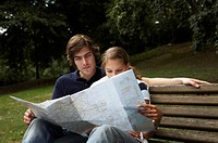 Junges Paar auf einer Parkbank mit Landkarte, young couple sitting on a park bench with a map