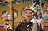 Senior man with a prayer wheel in a monastery, Likir Monastery, Ladakh, Jammu and Kashmir, India