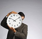 Businessman hiding his face with a clock