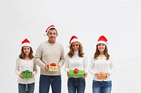 Family with two daughters 10_11, 16_17 holding presents in studio