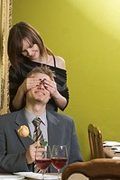 Woman covering man´s eyes at restaurant table