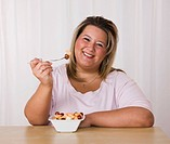 Portrait of smiling young woman eating fruit salad