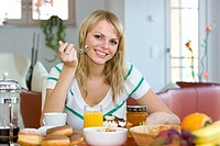 Portrait of woman having breakfast and smiling at table