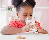African girl drinking milk with cookie